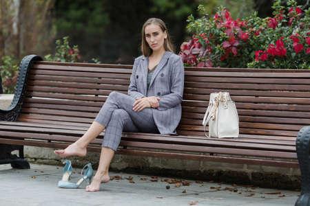 Empresaria en traje gris descansando sobre un banco en el parque. Mujer descalza se sienta en un banco en el parque y mirando a la cámara