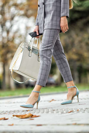 Womans feet on the street. Attractive businesswoman in gray suit  walks along autumn park Stok Fotoğraf