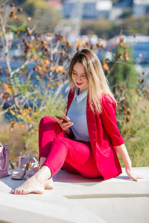 Portrait of resting girl in suit. Barefoot young woman sits on retaining wall and communicates by smartphone