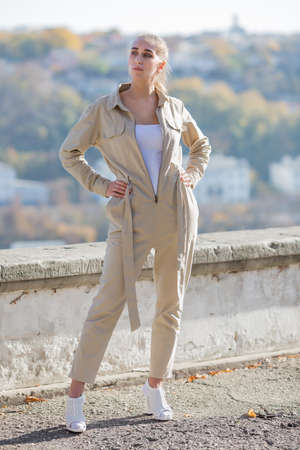Portrait of blonde person in unbuttoned jumpsuit in public Park. Attractive young woman in sunglasses and overalls similar to the uniform posing against retaining wall park with arms akimbo