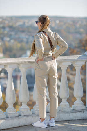 Long-haired girl looks at the city from the observation deck. Young woman with ponytail stands with hands on loin and looks into distance, rear view