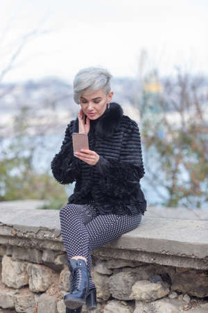 Girl in fur coat sitting on retaining wall. Young woman sits with legs crossed and communicates by smartphone