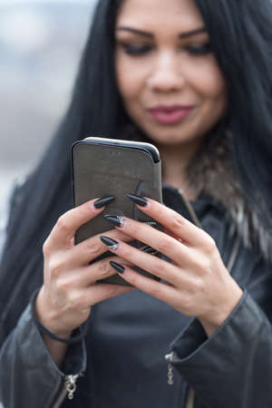Portrait of long haired brunette on open air. Young woman in monochrome closes communicates by smartphone. Phocus on foreground