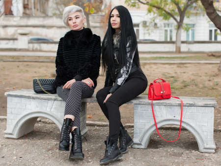 Two city girls in a public Park. Two young attractive women in dark autumn clothes sit on bench in park looking at camera