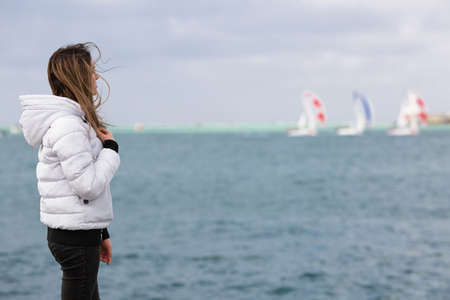 Late teen girl observing yacht regatta in windy day. Young female person stands on seashore and looks away, side view