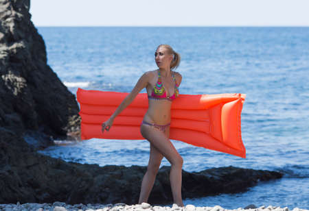 Girl resting at the sea. Young woman in swimwear walks along coast carrying inflatable pool raft