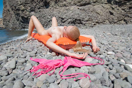 Slim young woman resting on wild shingle beach. Naked blonde-haired female person sunbathes lying on back on inflatable pool raft. Her bikini drying on heat pebble