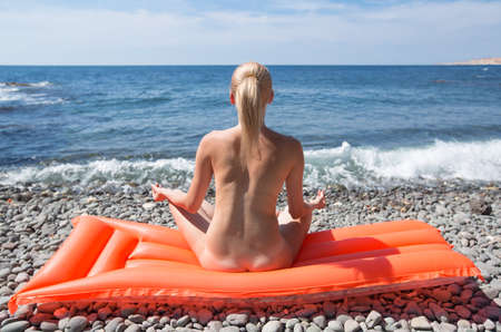 Slim young woman resting on wild shingle beach. Naked blonde-haired female person sunbathes sitting cross-legged on inflatable pool raft against sea, rear view