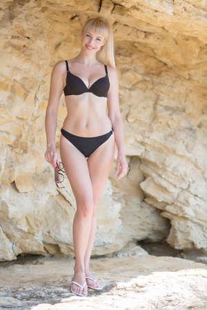 Girl on wild rocky seashore. Pretty blonde in black bikini holding sunglasses and smiling Stok Fotoğraf