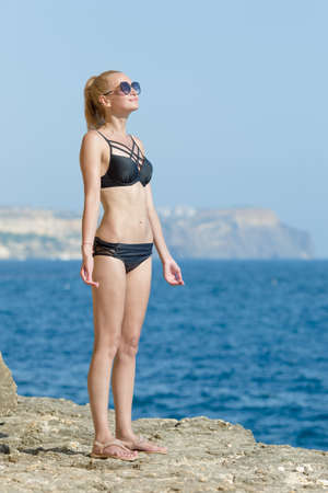 Woman sunbathing by the sea. Attractive female person in black swimsuit standing on rocky seashore and turns herself to the sun on background of blue water Фото со стока