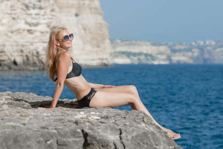 Young woman on wild rocky beach. Attractive female person in black  bikini sitting on the sea edge, looking away through sunglasses and smiling