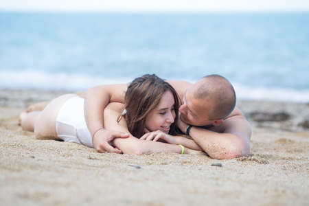 Attractive couple relaxing by the sea. Young man embracing his girlfriend lying on front on sandy beach and smiling
