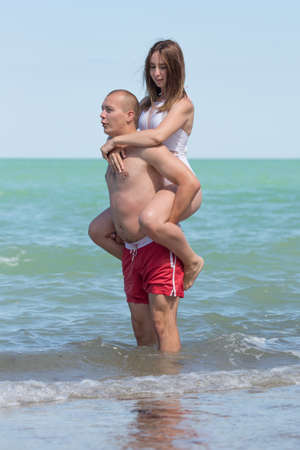 Piggyback. Young man carries girl on his back standing in shallow sea water