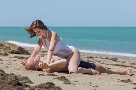 Young woman in white swimwear sits astride her bare-chested man and holds his hands to make him unable to move