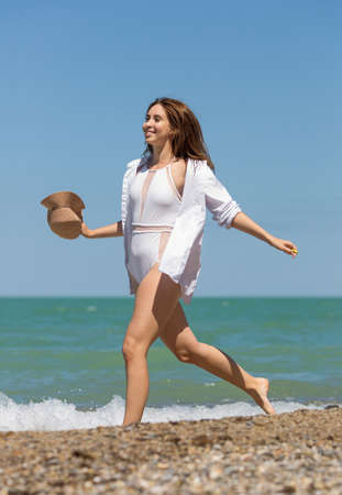 Young woman in one-piece swimsuit and white shirt running along seashore.