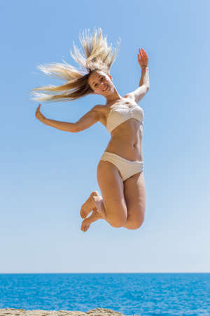 Girl at the sea. Happy young woman in white swimsuit jumping against sea Standard-Bild