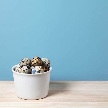 pigeon egg: Quail eggs on the table. Eggs on a turquoise background with copy space Diet food. Vitamin product