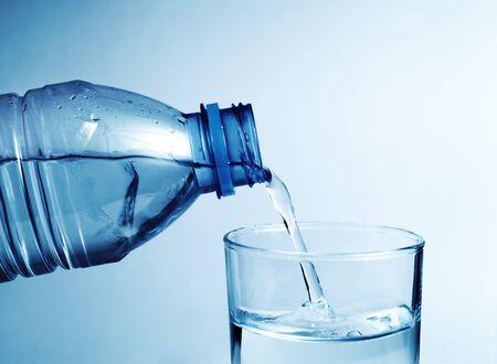 vaso de agua: Botella de agua fr�a vierta agua al vidrio con poca profundidad de campo Foto de archivo