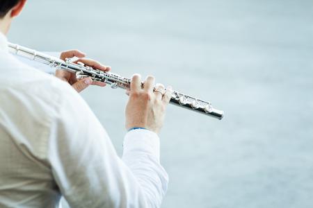 flauta: músico que toca la flauta en un fondo neutro Foto de archivo