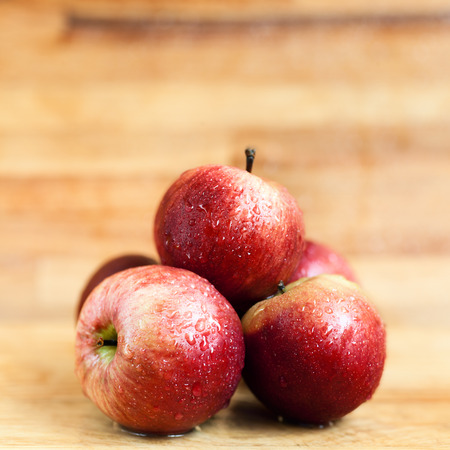 Red apples on wooden background Foto de archivo