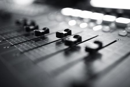 aparatos electricos: Consola de mezcla de audio profesional con faders y botones de ajuste, equipos de televisi�n y Negro Blanco enfoque selectivo Foto de archivo