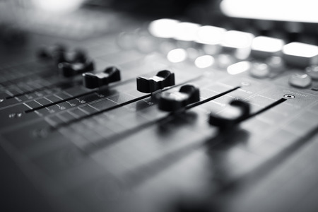 Professional audio mixing console with faders and adjusting knobs,TV equipment Black and White selective focus photo