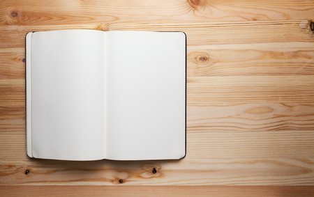 otevřená kniha s prázdnými stránkami na dřevěný stůl, notebook na dřevěný stůl na pozadí prostor pro text