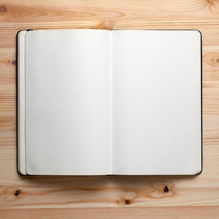Open notebook on a wooden table,blank notepad with empty white pages