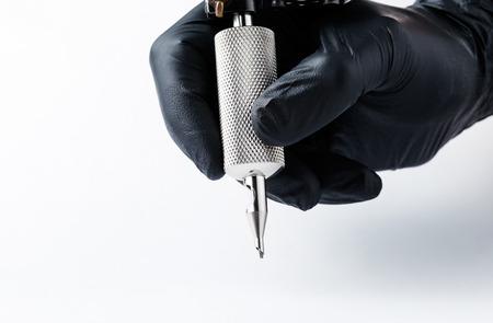 Tatoeëerder maakt een tatoeage. Close-up, Tattoo kunstenaar aan het werk Machine voor tatoeage op een witte achtergrond