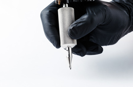 Tattooist makes a tattoo. Closeup,Tattoo artist at work Machine for tattoo on white background