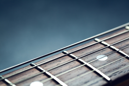 fret: Guitar neck closeup, strings, guitar background abstract guitar music rosewood fret board selective focus point, shallow depth of field