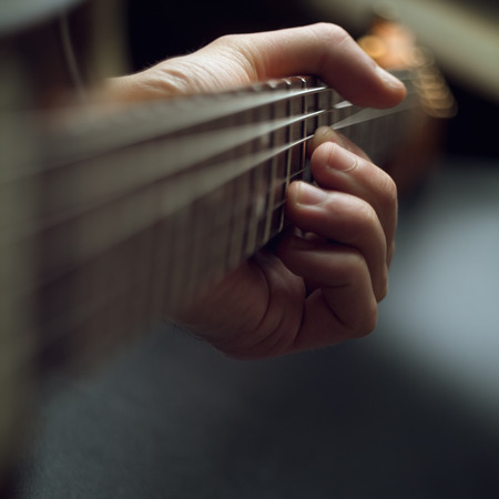 frets: playing guitar, close up Hands of man playing electric guitar selective focus
