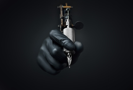 machines: Tattoo artist holding tattoo machine on dark background, Machine for a tattoo concept Stock Photo
