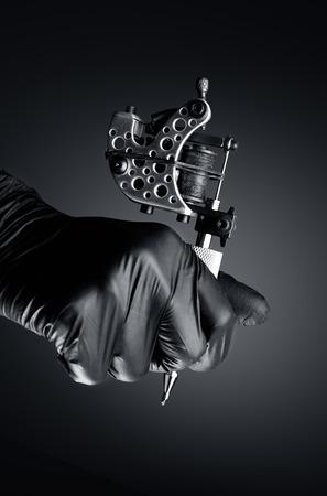 Tattoo artist holding tattoo machine, Machine for a tattoo concept dark background,tattoo machine in hand Foto de archivo
