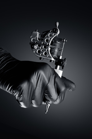 pistola: Artista del tatuaje que sostiene la máquina del tatuaje, Máquina para un tatuaje concepto fondo oscuro, máquina de tatuaje en la mano Foto de archivo