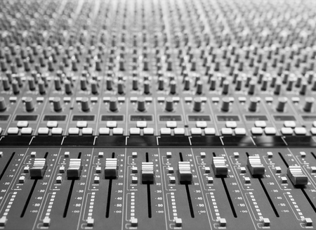 decibel: Professional sound music mixer control panel console with faders and adjusting knobs,TV equipment Black and White selective focus