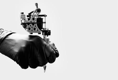 Tattoo-Künstler mit Tattoo-Maschine auf hellgrauem Hintergrund
