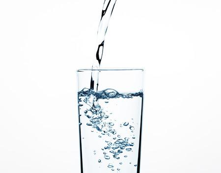 Verser de l'eau dans un verre en gros, des éclaboussures d'eau du verre Banque d'images
