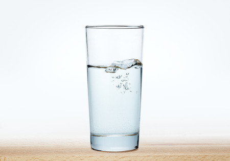 glass cup: glass of water on a wood table,water in glass on  wood