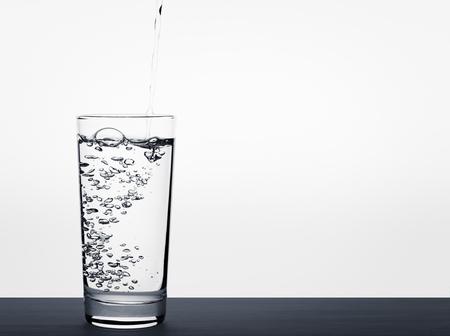 Versando acqua in un bicchiere spruzzi d'acqua da vetro adatto per lo spazio della copia