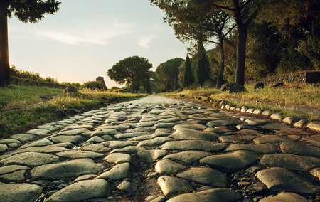 Antique road , Via Appia Antica in Rome, Italy on sunset 스톡 콘텐츠