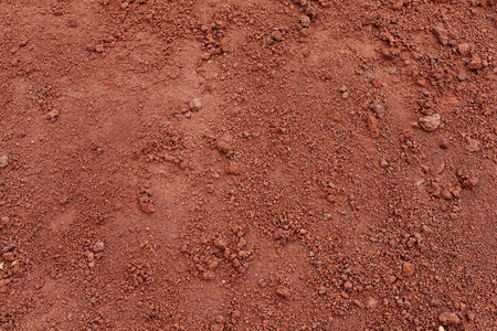 Red Soil Tropical laterite soil or red earth background. Red mars sand background. Top view Stok Fotoğraf