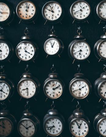 top seven: many retro alarm clocks on dark background, time concept