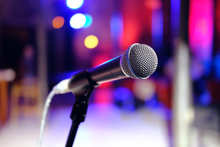 concert background: Close up of microphone in concert hall or conference room on colorful blurred background