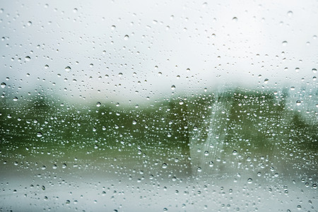 Raindrops stuck on glass windows with blur paddy field background