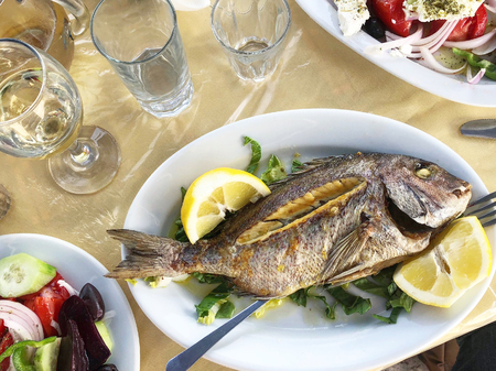 Grilled fish with lemon and vegetables on the plate