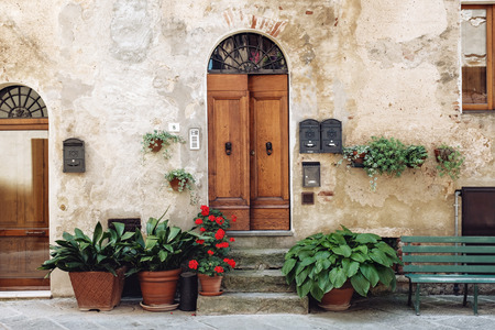 facade with flowers in beautiful courtyard in Tuscany, Italy in summer day, plants surround doorway
