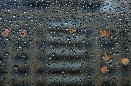 raindrops on window glass surface with night city background