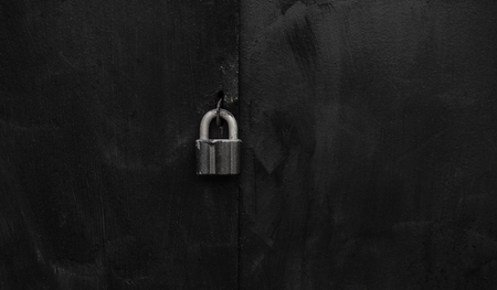 locked big massive black padlock on metal door background close up