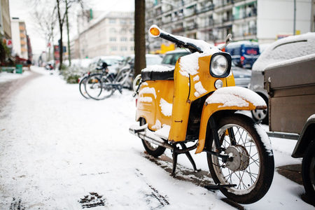 old classic vintage yellow motor scooter  covered snow on a winter city background